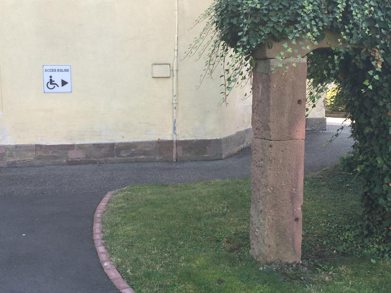 Panneau directionnel vers entrée PMR sur façade
