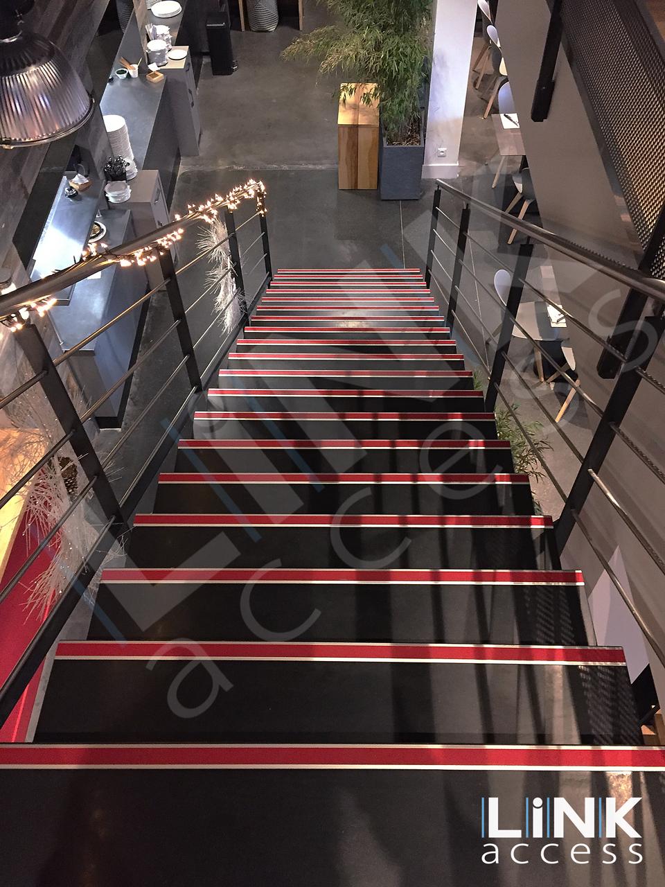 escalier aux normes accessibilité grâce à ses nez de marche rouge.