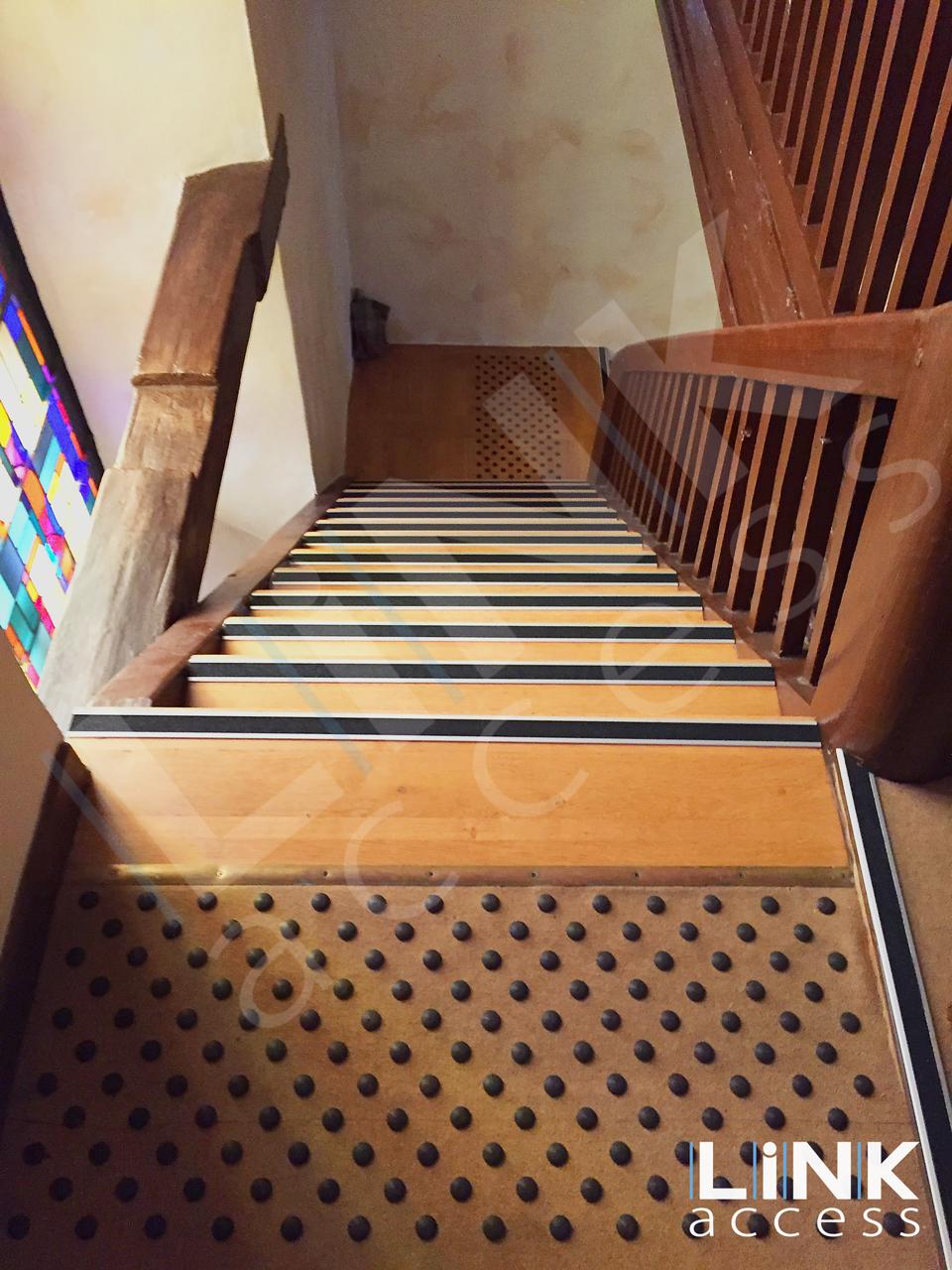 Escalier en bois équipés de nez de marche noir et de ses bandes d'éveil à la vigilance obligatoires.