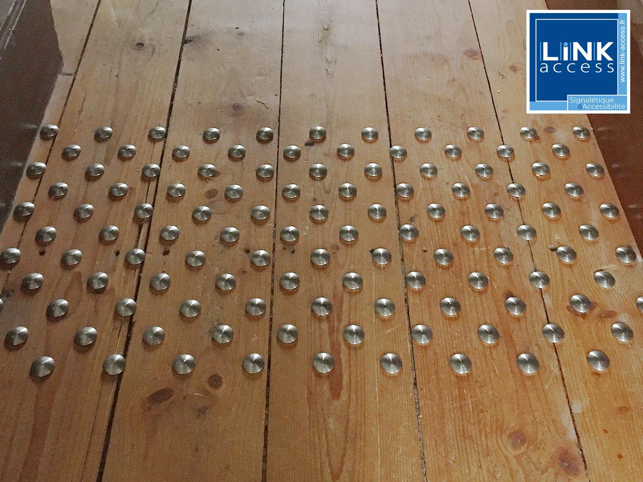 Clous podotactiles constituant une bande d'éveil à la vigilance avant un escalier dans une église à Lampertheim.