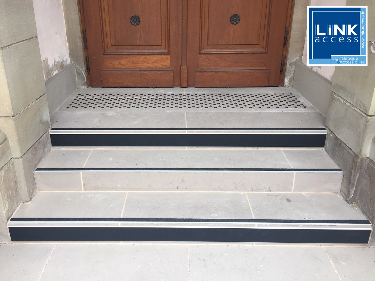 Clous podotactiles formant une bande d'éveil, Nez de marche et contremarches contrastée ont été installés sur ces marches pour sa mise en conformité accessibilité.