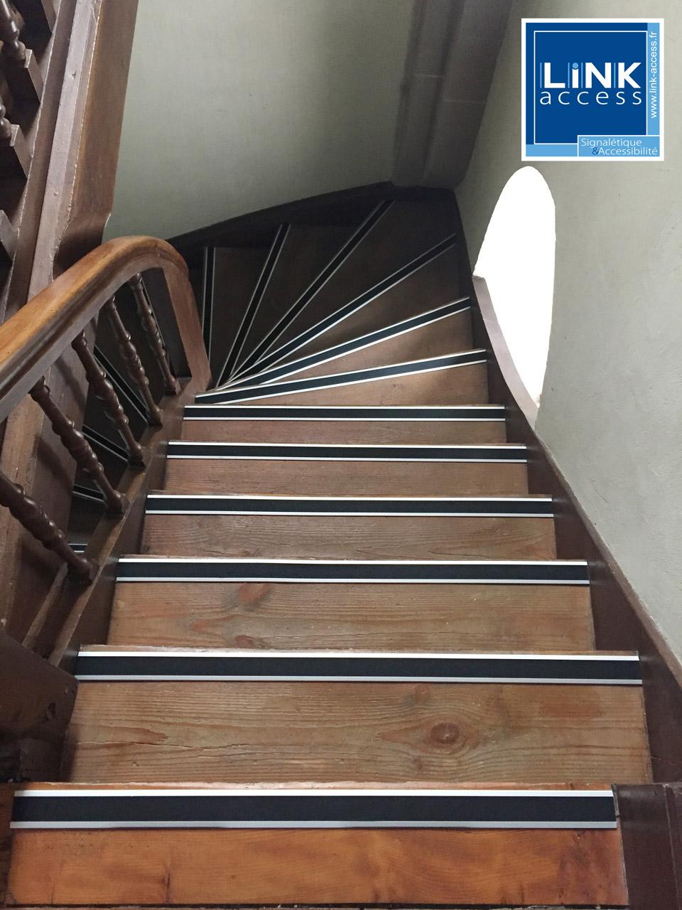Nez de marche contrastés antidérapants noirs sur un escalier en bois par Link-Access.