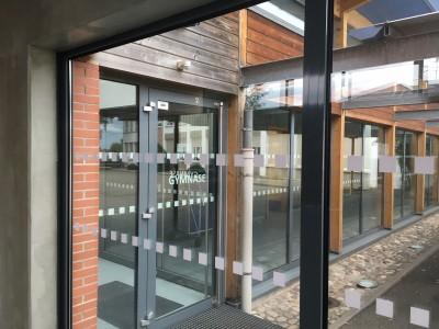 les vitres de l'entrée du gymnase ont été sécurisé a l'aide de bandes adhésives.
